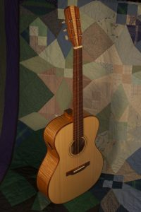 Orchestra guitar no 14 features red maple sides and back and an Adirondack spruce top.