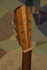 Orchestra guitar no 15 headstock front in palo escrito with a maple wedge.