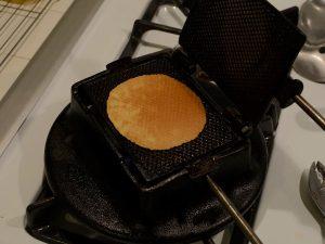 An open lukken iron showing a baked cookie.