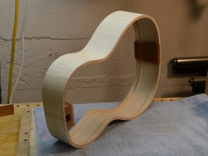 A completed rib assembly for a small body guitar in curly sugar maple.