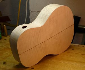 View of the maple back and sides. The opening in the side is a sound port.