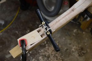 I work the neck with a spokeshave, forming facets that echo the general profile to be refined later by rasp.