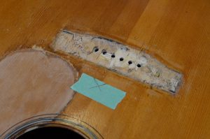 The top of a guitar, under the removed bridge