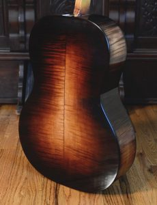 The grand concert's sugar maple back is colored with dyes and toned shellac.