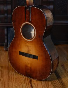 The grand concert's adirondack spruce top looks sharp with the African blackwood bridge.